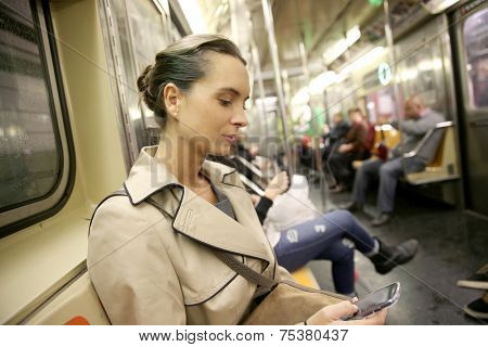 Businesswoman in subway reading message on smartphone