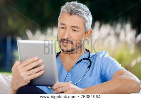Male caretaker using tablet PC while sitting at nursing home porch