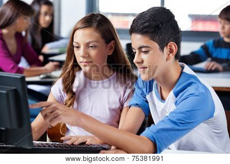 Teenage boy with female friend pointing at computer screen in classroom