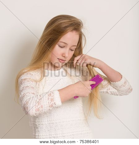 Pretty Young Blond Girl Brushing Her Hair