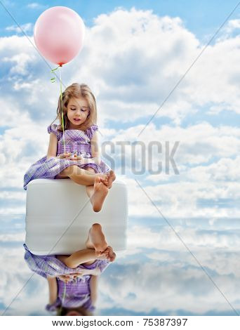 little girl holding pink balloon