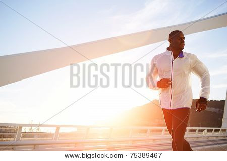 Male runner in windbreaker jogging over bridge road at sunset