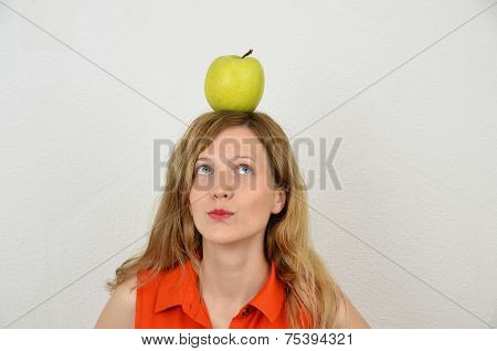 Young blonde girl with green apple on the head