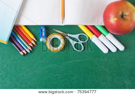 School supplies and apple on the chalkboard
