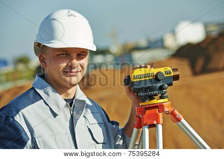 Surveyor builder worker with level equipment at construction site outdoors during surveying work