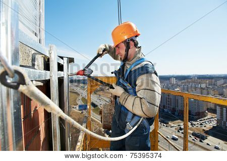 worker builder clinching facade construction for big tile on a building with riveting hammer