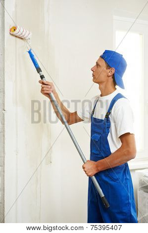 painter with paint roller making wall prime coating  at home repair renovation work