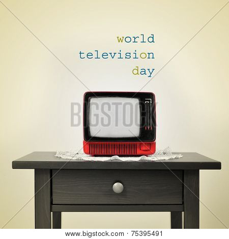 an ancient red television on a table and the sentence world television day on a beige background, with a retro effect