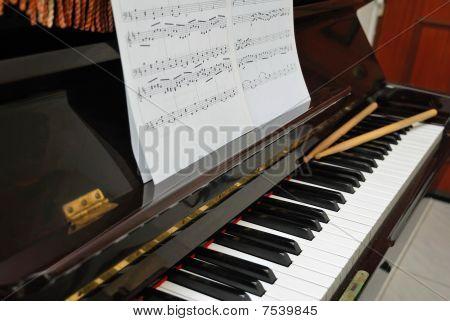 Music Score And Drum Sticks On Piano Keyboard