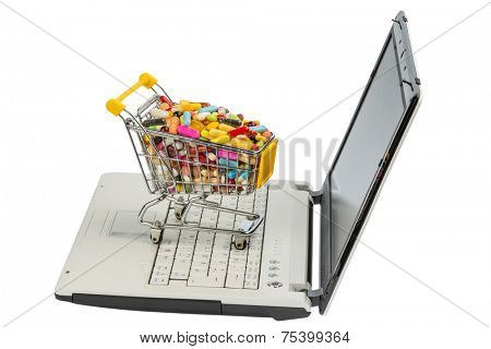 tablets with shopping cart and computer. symbol photo for the purchase of medicines on the internet