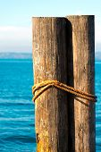 picture of bollard  - Detail of two wooden bollards with rope at Garda Lake in Italy - JPG