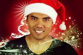 stock photo of filipino  - young Filipino with a hat of Santa Claus on a red background - JPG