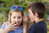stock photo of pimp  - boy and girl counting a secret to the ear - JPG