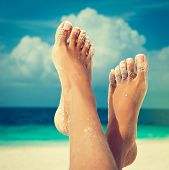 stock photo of sun-tanned  - Tanned feet with pedicure with white Sands and the turquoise sea and blue sky - JPG