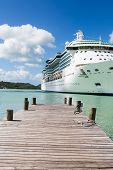 pic of cruise ship caribbean  - Rope coiled on an old wooden pier with a white luxury cruise ship in the background - JPG