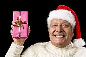 foto of oblong  - Upbeat smiling male senior lifting up an oblong present wrapped in pink and decorated with golden bowknot - JPG