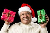 picture of coy  - Honorable old man with Santa Claus cap his showing a red and a green wrapped present - JPG