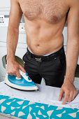 foto of laundromat  - Midsection of shirtless man ironing shirt on table at laundromat - JPG