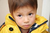 stock photo of straight jacket  - Sadly cute boy portrait in the yellow jacket - JPG