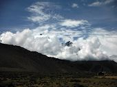 picture of mustang  - Heavy monsoon clouds building up before some snowy Himalayan peaks in the dry landscape of the Mustang Annapurna region of Nepal - JPG