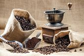 picture of coffee grounds  - still life of coffee beans in jute bags with coffee grinder - JPG