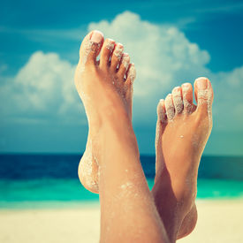 pic of pedicure  - Tanned feet with pedicure with white Sands and the turquoise sea and blue sky - JPG