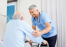 foto of zimmer frame  - Smiling male caretaker helping senior man to use walking frame in bedroom at nursing home - JPG