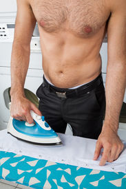 pic of laundromat  - Midsection of shirtless man ironing shirt on table at laundromat - JPG