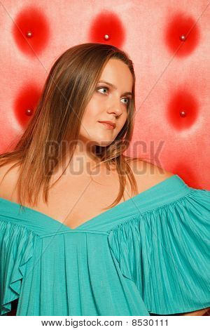 woman in a turquoise dress near to a red wall