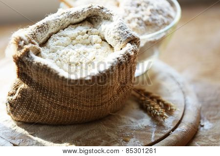 Flour in burlap bag with cutting board on wooden background