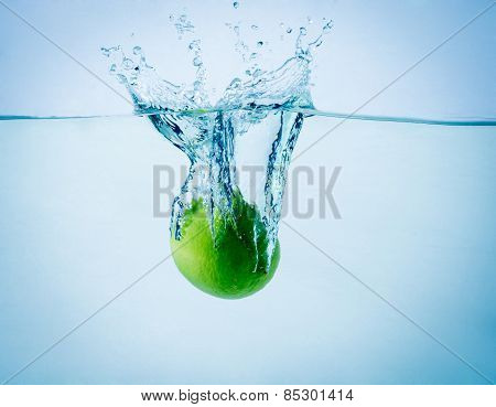 High speed freeze action shot of a lime splashing in water on white background