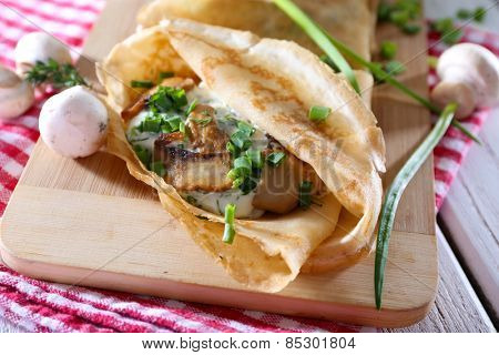 Pancakes with creamy mushrooms on cutting board on wooden table, closeup