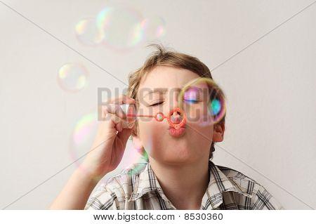 Menino caucasiano soprando bolhas de sabão no fundo branco, vista frontal