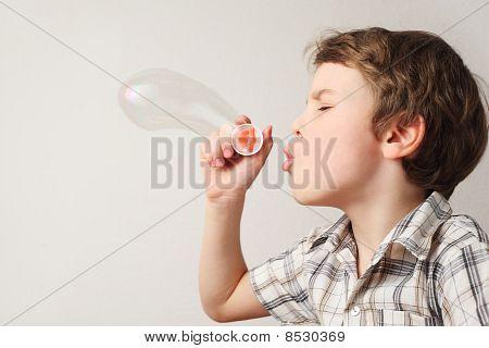 Little Caucasian Boy Blowing Soap Bubbles On White Background, Side View