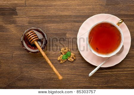 Top view of tea honey and nuts with mint on wooden background