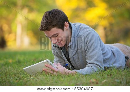 Happy Teen Writing On Grass