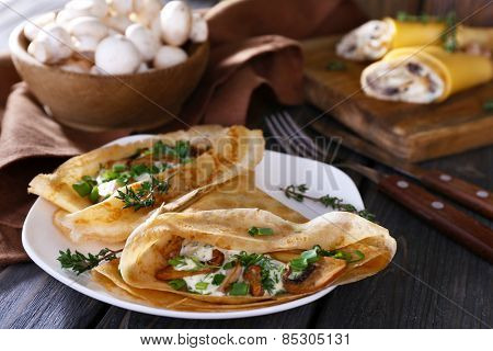 Pancakes with creamy mushrooms on wooden table, closeup