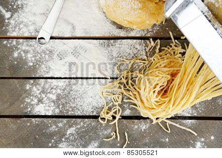 Making vermicelli with pasta machine on wooden table with flour, top view