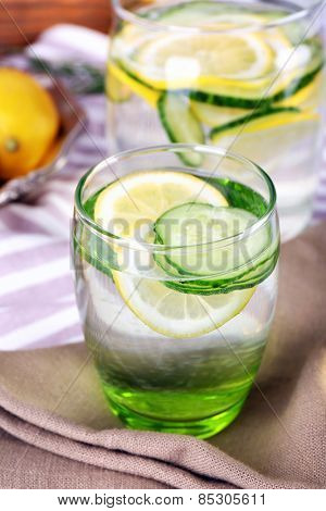 Fresh water with lemon and cucumber in glassware on napkins, closeup