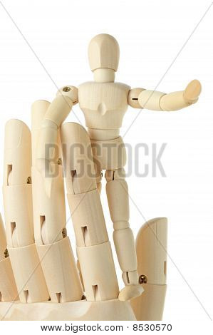 Wooden Figure Of Little Man Standing On Big Hand And Pointing At Right, Front View, Isolated