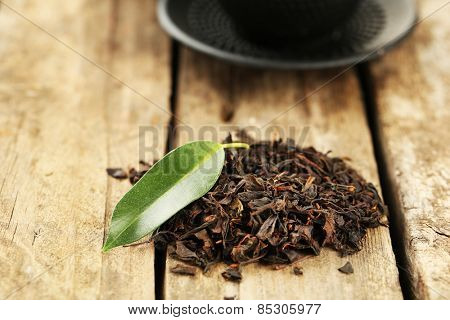 Black tea with leaf on old wooden table