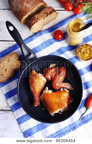 Smoked chicken with vegetables and mustard on pan on table close up