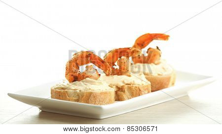 Appetizer canape with shrimp on plate isolated on white