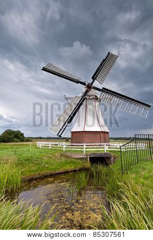 White Windmill By River Over Clouded Sky
