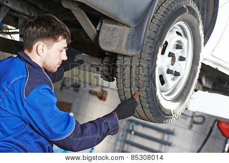auto service man worker measuring rubber car wheel tyre protector