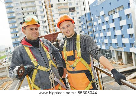 Team of smiling facade builders workers in protective uniform at construction building site
