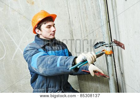 industrial plumber fixing pipe in water heating engineering system of building