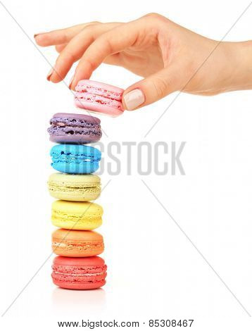 Tasty colorful macaroons and female hand isolated on white