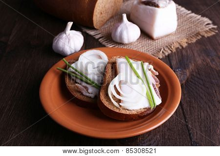 Sandwiches with lard on plate and garlic on wooden background