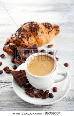 Fresh and tasty croissants with chocolate and cup of coffee on color wooden background